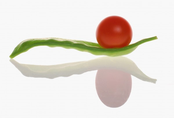 A cherry tomatoe on snow pea with reflection